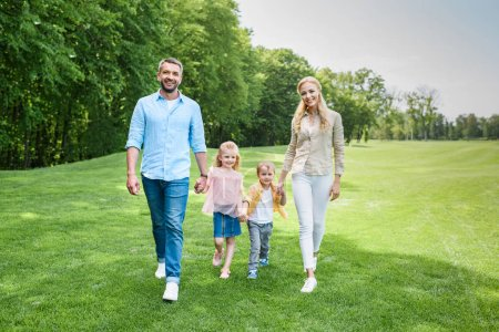 happy family holding hands and smiling at camera while walking together in park
