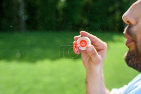 cropped shot of bearded man blowing soap bubbles in park