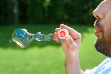 side view of bearded man blowing soap bubbles in park