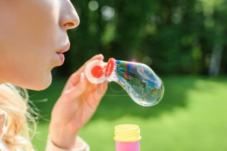 cropped shot of young woman blowing soap bubbles in park