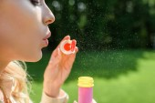 side view of young woman blowing soap bubbles in park