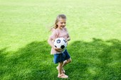 high angle view of happy little child holding soccer ball on grass