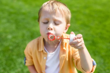 Photo for Cute little boy with closed eyes blowing soap bubbles in park - Royalty Free Image