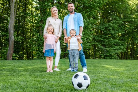 soccer ball on grass and happy family standing together in park