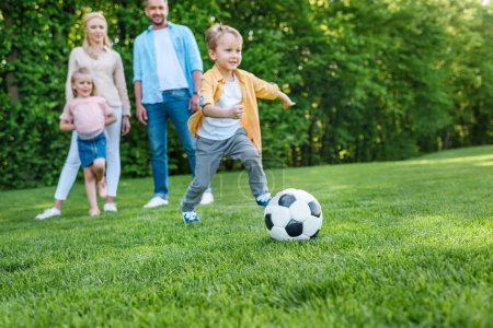 family looking at little boy playing with soccer ball in park
