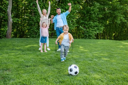 happy family playing with soccer ball in park