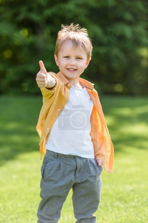 cute happy little boy showing thumb up and smiling at camera in park