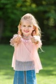 cute little child showing thumbs up and smiling at camera
