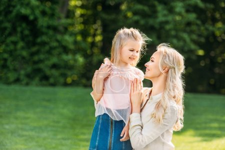 Photo for Beautiful happy mother and daughter smiling each other in park - Royalty Free Image