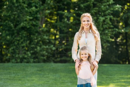 beautiful happy mother and daughter standing together and smiling at camera in park
