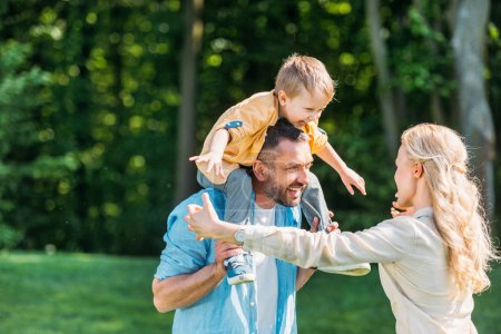 happy parents with adorable little son spending time together in park