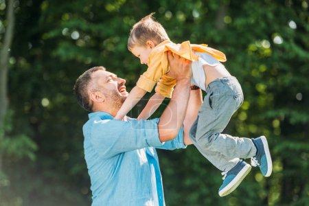 Photo pour Heureux père portant adorable petit fils dans le parc - image libre de droit