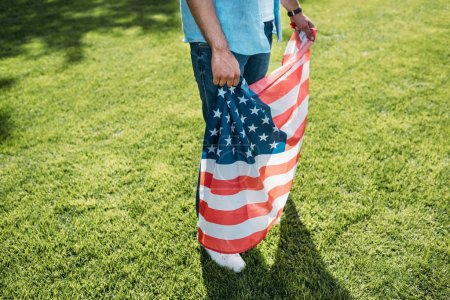cropped shot of man holding american flag while standing on grass in park