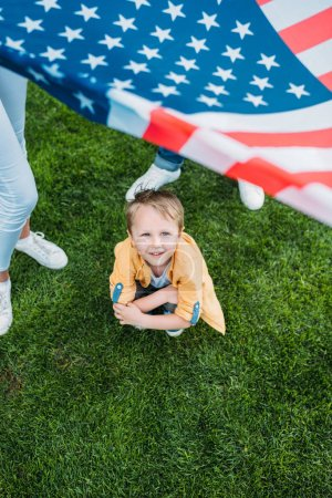 cropped shot of parents holding american flag and little son crouching on grass