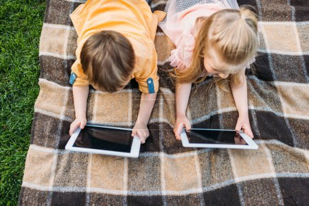 overhead view of cute little kids using digital tablets while lying on plaid