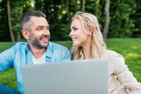 Photo for Happy couple using laptop and smiling each other in park - Royalty Free Image
