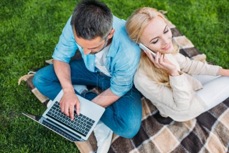 Photo for High angle view of happy couple using smartphone and laptop in park - Royalty Free Image