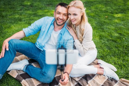 Photo for Happy young couple taking selfie with smartphone at picnic - Royalty Free Image