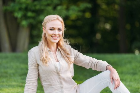 hermosa joven sentada y sonriendo a la cámara en el parque
