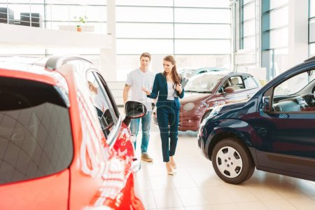 front view of woman with clipboard showing automobile to male client in car showroom