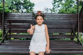 portrait of cute little kid showing thumb up while resting on wooden bench in summer day