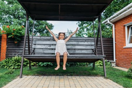 Photo for Cute little kid with outstretched arms resting on wooden bench in summer day - Royalty Free Image