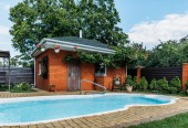 wooden country house with swimming pool near by, trees and cloudy sky