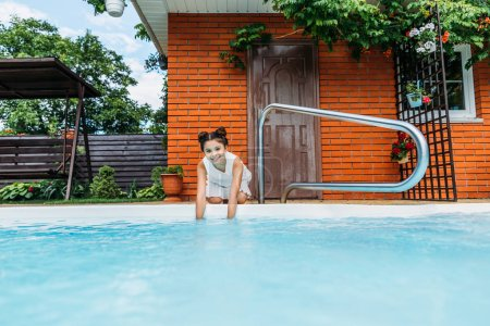 adorable smiling child at swimming pool near country house
