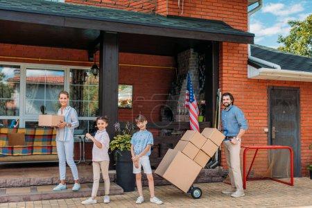 Photo pour Parents avec des boîtes en carton et des enfants debout à la maison de campagne, se déplaçant de maison concept - image libre de droit