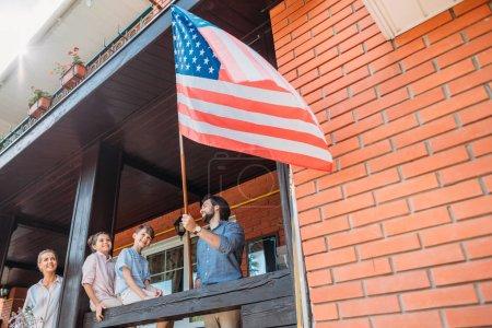 family with american flag standing on country house porch