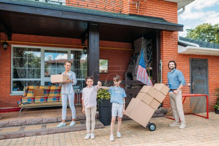 children with keys and parents with cardboard boxes standing at country house, moving home concept