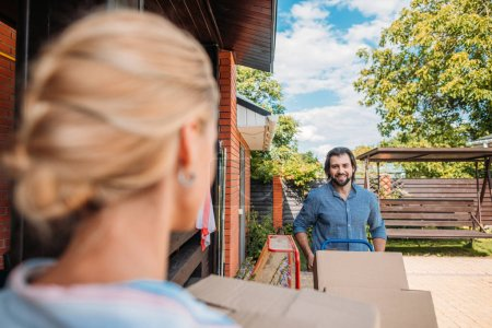 selective focus of man with handle tray with cardboard boxes looking at wife at new house, moving home concept