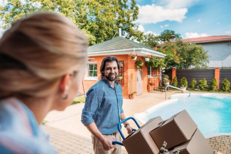 smiling man with handle tray with cardboard boxes looking at wife on porch of new house, moving home concept