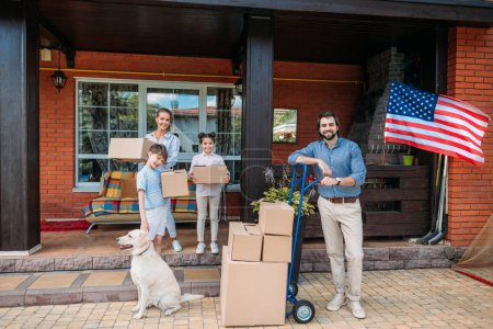 Photo for Family with cardboard boxes and labrador dog standing on country house porch, moving home concept - Royalty Free Image