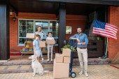 family with cardboard boxes and labrador dog standing on country house porch, moving home concept