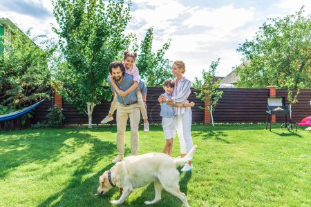 Photo for Cheerful family with labrador dog spending time together on backyard on summer day - Royalty Free Image
