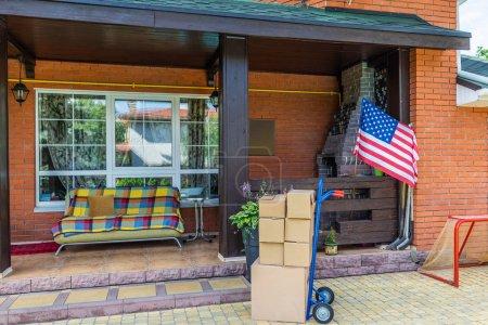 Photo pour Camion à main avec boîtes en carton et canapé sur le porche de la maison de campagne - image libre de droit