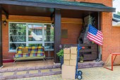 hand truck with cardboard boxes and sofa on porch of country house