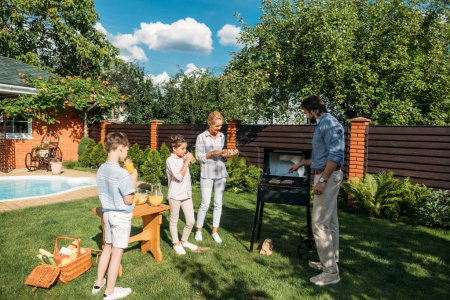 familia teniendo barbacoa juntos en el patio trasero en el día de verano