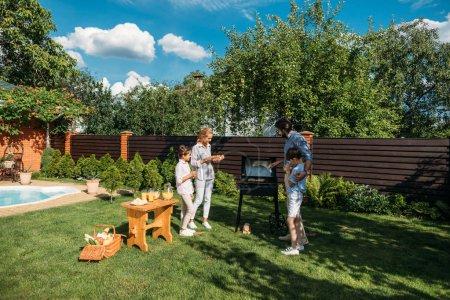Photo pour Famille ayant barbecue ensemble sur la cour le jour d'été - image libre de droit