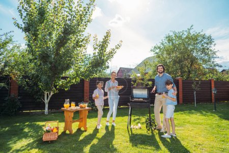 family having barbecue together on backyard on summer day