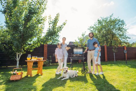 family with dog having barbecue together on backyard on summer day
