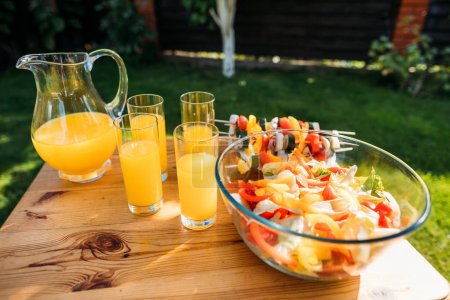 close up view of glasses of juice and salad with fresh vegetables on wooden surface on backyard