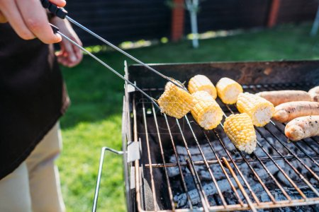 partial view of man cooking corn and sausages on barbecue on summer day