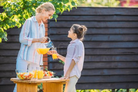 side view of smiling mother pouring juice into daughters glass during picnic on backyard