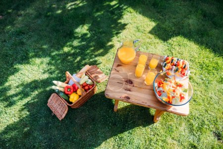 top view of basket with food for picnic, glasses of  juice and fresh salad on wooden chair on green lawn