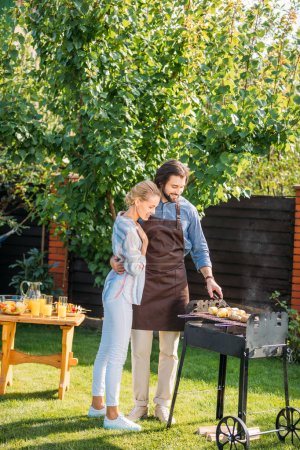 smiling couple having barbecue on backyard on summer day