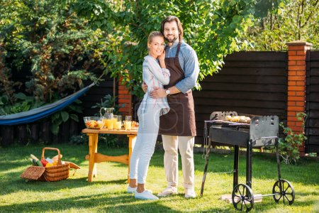 smiling couple looking at camera having barbecue on backyard on summer day