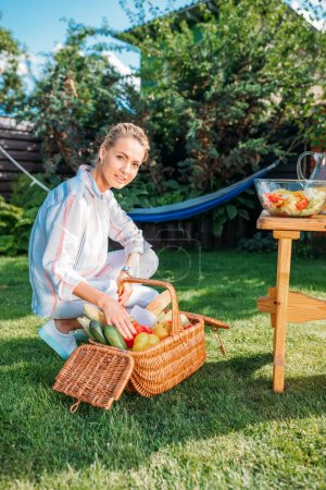 woman with basket full of fresh vegetables for picnic on backyard