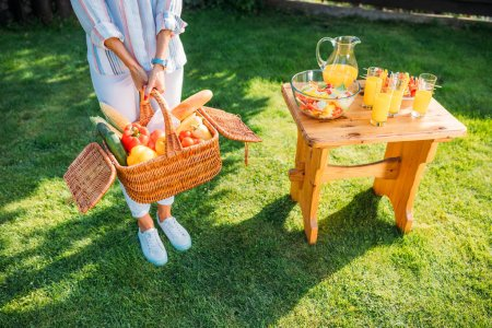 cropped shot of woman with basket full of fresh vegetables for picnic on backyard